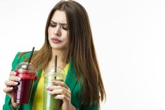 Healthy Food Eating. Woman Drinking Both Green and Red Detox Vegetable Smoothie. Posing in Green Jacket Over White. Unpleased Facial Expression. Horizontal stock images