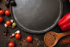 Healthy food and empty plate top view. Close up background of vegetables and spices, free space black dish. Recipe, cuisine and menu concept Royalty Free Stock Images