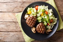 Healthy food: filet mignon steak with mushrooms and vegetable sa. Healthy food: filet mignon steak with mushrooms and fresh vegetable salad close-up on a plate stock photo