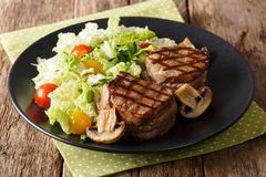 Healthy food: filet mignon steak with mushrooms and vegetable sa. Healthy food: filet mignon steak with mushrooms and fresh vegetable salad close-up on a plate stock photography