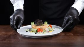 Healthy food and fine restaurant cuisine. Chef in black gloves holding plate with cooked tartar on black background stock video