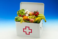 Healthy food. First aid box filled with fruits and vegetables. Healty food. First aid box filled with fresh fruits and vegetables on blue background Royalty Free Stock Photo