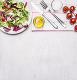 Healthy food fresh salad on a white plate with oil and salt, a knife and fork  napkin border ,place for text  on wooden rustic Royalty Free Stock Photos