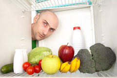 Healthy food in fridge. Portrait of young man looking at different healthy food inside refrigerator royalty free stock photos