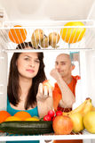 Healthy food in fridge. Young couple eating and looking at healthy fruit and vegetable in modern refrigerator, isolated on white background stock image
