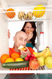 Healthy food in fridge. Young couple eating and looking at healthy fruit and vegetable in modern refrigerator, isolated on white background royalty free stock photo