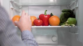 Healthy Food in the Fridge. Timelapse of man substituting unhealthy sandwich with fresh and nutritious fruit and vegetables, concept of eating healthy food stock footage