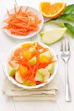 Healthy food. Fruit salad. With carrots, apples, bananas in bowl on white wooden table Royalty Free Stock Photos