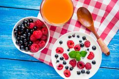 Healthy food with fruit and yoghurt. Sweet breakfast with healthy food with fruit and yoghurt on blue wood table stock photos