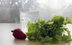 Healthy food, glass and next salad and strawberries. Healthy food, clean water in a glass and next to lie a green salad and strawberries royalty free stock photos