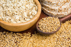 Healthy food, grains and seeds. Variety of grains: rolled oats, golden linseeds (flax seeds), whole wheat grains and buckwheat cakes. Soft focus. Merchendise Royalty Free Stock Image