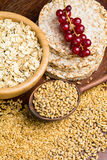 Healthy food, grains and seeds. Variety of grains: rolled oats, golden linseeds (flax seeds), whole wheat grains and buckwheat cakes. Soft focus. Merchendise Royalty Free Stock Photos