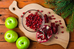 Healthy food: green apple and grenades on a wooden table. Royalty Free Stock Image