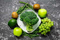 Healthy food with green vegetables, fruits for dinner on dark table background top view. Healthy food with green vegetables, fruits for fitness dinner on dark royalty free stock image