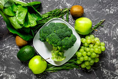 Healthy food with green vegetables, fruits for dinner on dark table background top view. Healthy food with green vegetables, fruits for fitness dinner on dark stock image
