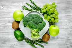 Healthy food with green vegetables, fruits for dinner on gray table background top view. Healthy food with green vegetables, fruits for fitness dinner on gray Stock Image