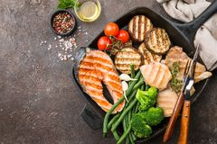 Healthy grill food. Healthy food - grilled salmon steak, chicken and vegetables over dark background, top view stock photos