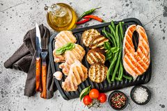 Healthy grill food. Healthy food - grilled salmon steak, chicken and vegetables over gray background, top view stock photos