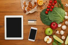 Healthy food, grocery online shopping. Copy space on mobile and tablet screen. Fresh organic vegetables and fruits on wood table, top view, flat lay royalty free stock images