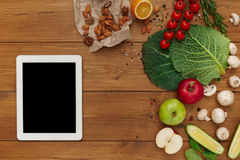 Healthy food, grocery online shopping. Copy space on tablet screen. Fresh organic vegetables and fruits on wood table, top view, flat lay Stock Images
