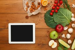 Healthy food, grocery online shopping. Copy space on tablet screen. Fresh organic vegetables and fruits on wood table, top view, flat lay stock photography
