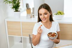 Healthy Food. Happy Woman Eating Nuts. Holding Plate In Hands. Portrait Of Beautiful Smiling Female ON Diet With Raw Organic Almonds In Hands In Kitchen royalty free stock photos