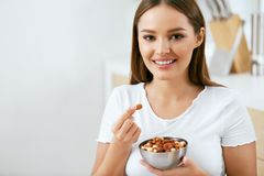 Healthy Food. Happy Woman Eating Nuts. Holding Plate In Hands. Portrait Of Beautiful Smiling Female ON Diet With Raw Organic Almonds In Hands In Kitchen royalty free stock images