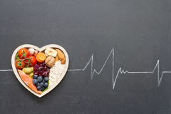 Healthy food in heart and cardiograph on blackboard Royalty Free Stock Photos