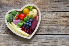 Healthy food in heart diet cooking concept with fresh fruits and vegetables. On wooden board stock images