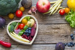 Healthy food in heart diet cooking concept with fresh fruits and vegetables. On wooden board stock image
