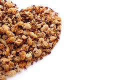 Healthy food, heart shape, white. Large size and good quality photo of various cereals and muesli: you may see closely different seeds, cereals and dried berries Royalty Free Stock Photography