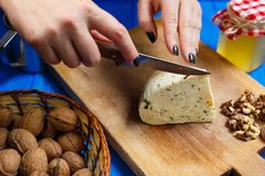 Woman hands cutting spicy homemade cheese on cutting board, serv. Healthy food, home cooking, cheese slices. Woman hands cutting spicy homemade cheese on cutting Royalty Free Stock Photo