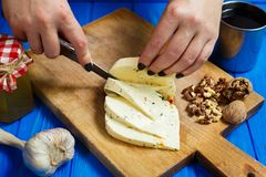 Woman hands cutting spicy homemade cheese on cutting board, serv. Healthy food, home cooking, cheese slices. Woman hands cutting spicy homemade cheese on cutting Royalty Free Stock Image