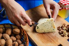 Woman hands cutting spicy homemade cheese on cutting board, serv. Healthy food, home cooking, cheese slices. Woman hands cutting spicy homemade cheese on cutting Stock Image