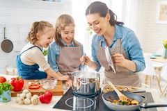 Happy family in the kitchen. Healthy food at home. Happy family in the kitchen. Mother and children daughters are preparing vegetables royalty free stock photography