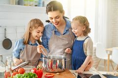 Happy family in the kitchen. Healthy food at home. Happy family in the kitchen. Mother and children daughters are preparing vegetables royalty free stock images