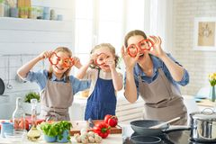 Happy family in the kitchen. Healthy food at home. Happy family in the kitchen. Mother and children daughters are preparing vegetables royalty free stock photos