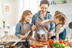 Happy family in the kitchen. Healthy food at home. Happy family in the kitchen. Mother and children daughters are preparing vegetables stock image