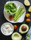 Healthy food ingredients - avocado, asparagus, tomatoes, sheep cheese, arugula on dark background, top view. Healthy clean eating. Concept Stock Image