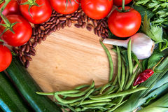 Healthy food ingredients. Frame of fresh vegetables on wooden background. Stock Image