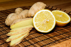 Healthy food. Lemon and ginger draped on a bamboo mat Stock Photos