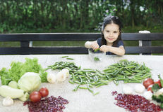 Healthy food. Little girl cleaning peas and recommend you to eat healthy food Royalty Free Stock Image