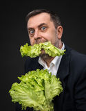 Man holding and eating lettuce Stock Photo