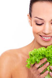 Healthy food for a natural beauty. Cropped shot of an attractive young woman holding a leafs of salad and smile over white isolated background Royalty Free Stock Photography