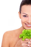 Healthy food for a natural beauty. Cropped shot of an attractive young woman holding a leafs of salad and smile to camera over white isolated background Royalty Free Stock Image