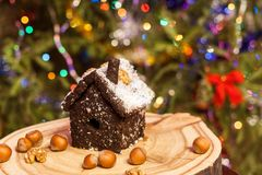 House made of crushed dried prunes, nuts, dates is standing on round wooden board on Christmas tree background. Healthy food. Natural sweetness. House made of stock images