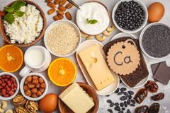 Healthy food nutrition dieting concept. Assortment of high calcium sources. Dairy products, legumes, eggs, nuts, chocolate, poppy royalty free stock photos