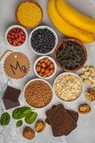 Healthy food nutrition dieting concept. Assortment of high magnesium sources. Banana chocolate spinach, buckwheat, nuts, beans, o
