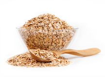 Healthy food. Oat flakes in glass bowl and spoon on white background Royalty Free Stock Photography