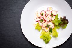 Healthy food organic slices radish salad in white plate on black. Slate board Stock Photos